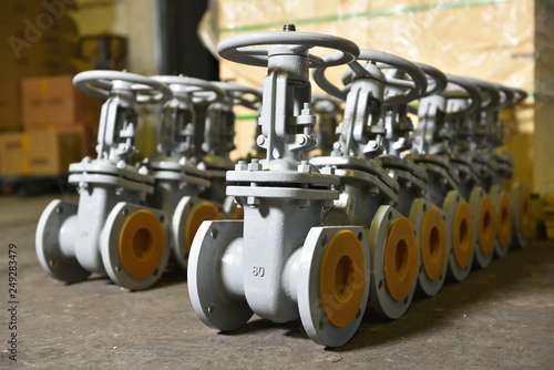Several new gray valves, for water or gas, lie on the floor at the factory Fototapet