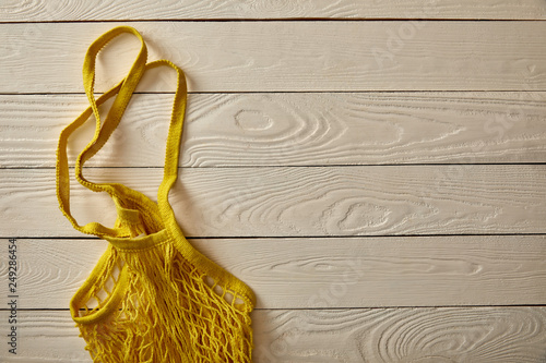 top view of empty yellow string bag on white wooden surface, zero waste concept