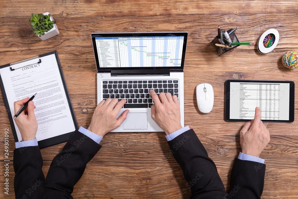 Fototapeta Businessman Doing Multitasking Work In Office