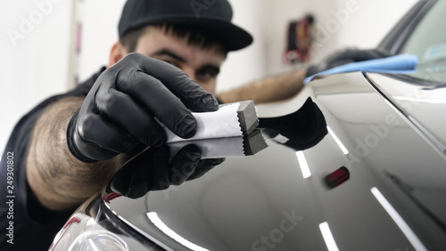 Professional ceramics handler apply different layers to the car using an applicator (sponge, fiber) immediately checking the effect. Concept from: Autodetailing, Special Ceramics, Nano technology.