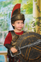 Little Boy Dressed As A Roman Soldier With A Sword, Helmet And Shield