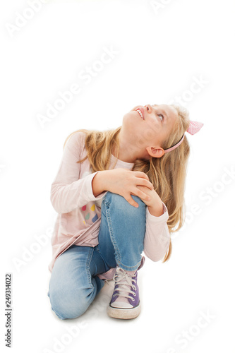 Portrait Of A Adorable Little Girl Sitting On The Knees Looking Up