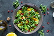 Green salad with avocado, orange and pomegranate in a bowl over dark background. Top view. Vegetarian and vegan food. Diet food.