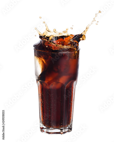 Fotografía  Cola splashing out of a glass isolated on white background