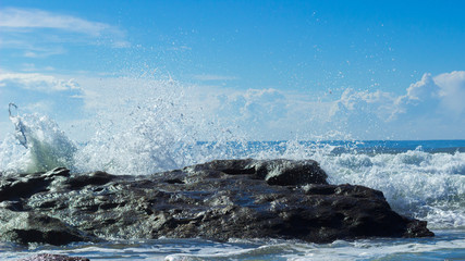 wave crashing over a rock with blue sky and clouds