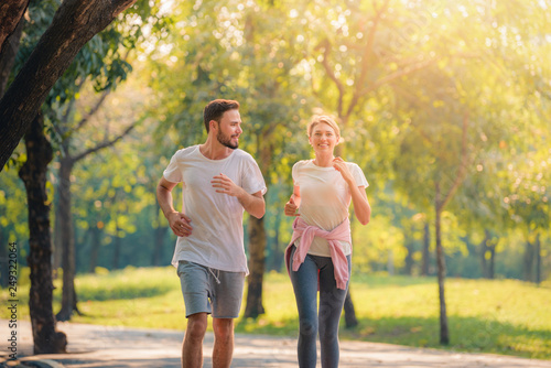 Poster Jogging Portrait of Young couple running in the park at sunset. Concept sport and love. Warm tone.
