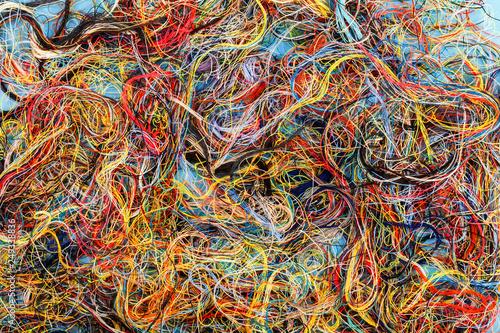 Obraz na plátně Colorful tangled threads on blue background. Closeup.