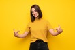 Young woman over yellow wall proud and self-satisfied