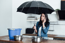 Shocked Woman With Umbrella Dealing With Water Damage In Kitchen And Talking On Smartphone