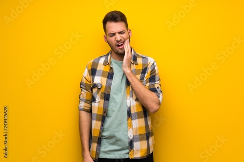 Stampa su Tela  Handsome man over yellow wall with toothache