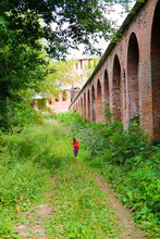 Happy Young Tourist Boy Runs Along The Red Brick Fortress Wall, Smolensk, Russia