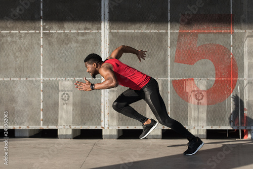 Fototapeta Young black urban athlete running and sprinting.