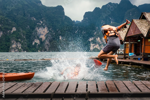 Foto  Young man jumping into the lake from the jetty