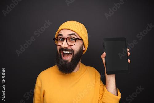 Amazed guy showing modern tablet