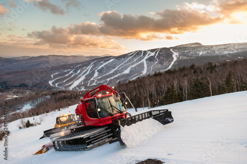 Photo  A fleet of snowcats grooming Spruce Peak at dusk with Mt