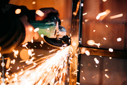 Fototapeta Close up details of sparks, industrial worker using angle grinder and cutting steel obraz
