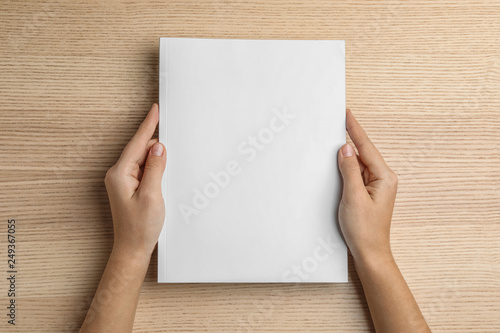 Fotografía  Woman holding brochure with blank cover on wooden background, top view