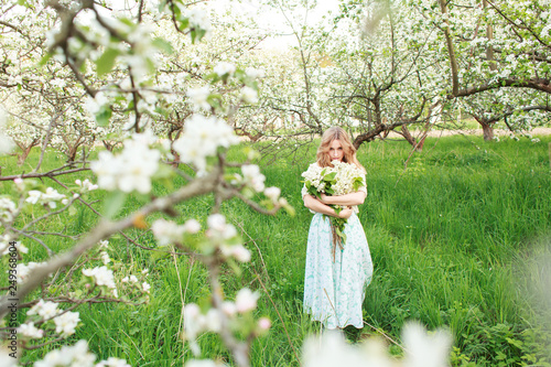 Poster Feeën en elfen Young beautiful blonde woman in a dress in blooming apple garden - outdoors