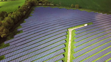 Solar Panels Farm Between Agriculture Fields In Aerial View.
