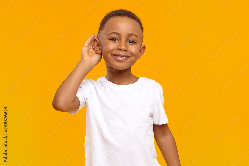 Fototapeta Body language, feelings and senses concept. Isolated view of cheerful dark skinned boy in white t-shirt smiling broadly and keeping hand at his ear while eavesdropping, overhearing, spying on someone