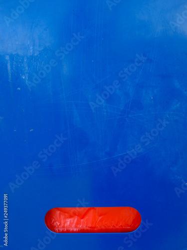 Fotografia  Red plastic stripe on generally blue background