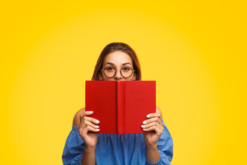 Obraz na SzkleWoman in glasses holding book near face