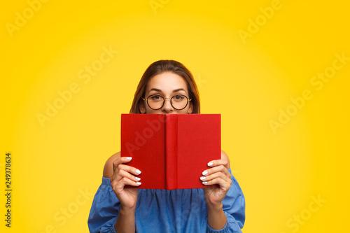 Fotografie, Obraz  Woman in glasses holding book near face