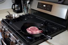 Ribeye Steak Frying In A Cast Iron Pan On A Natural Gas Stove Top.