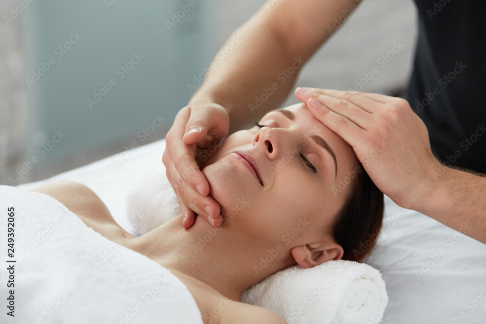 Fototapeta Young beautiful woman enjoying anti-aging facial massage.Male therapist making head massage to female client.Professional masseur.Relaxation,beauty,spa,body and face treatment concept.