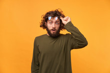 Student Saw Something Unusual, Curious, Incredible, And Even Raised His Glasses. Bearded Curly-haired Man Raised His Glasses Looking At The Camera His Mouth Opened In Surprise