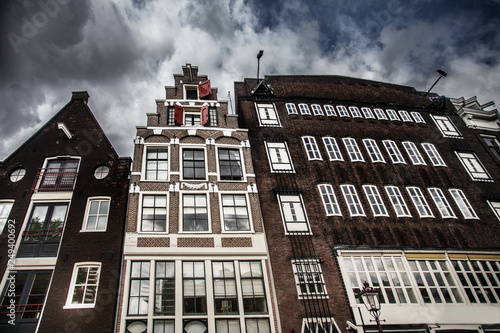 View of typical dutch architecture from Amsterdam under dramatic sky Wallpaper Mural