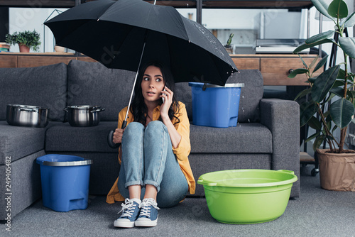 Fotografía  Girl in jeans sitting in living room with umbrella and talking on smartphone