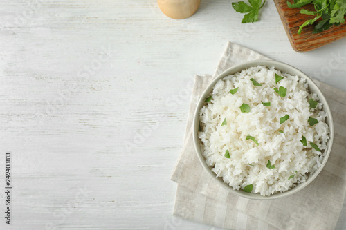 Fotografija Bowl of boiled rice served on wooden table, top view with space for text