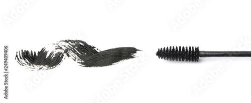 Valokuva  Applicator and black mascara smear for eyelashes on white background, top view