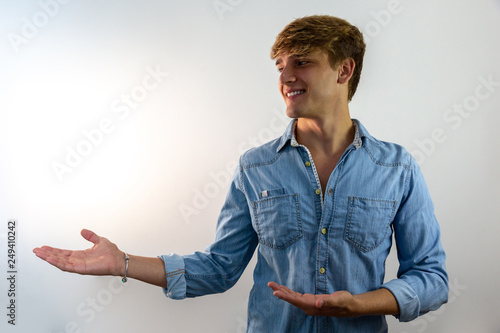 Photo  Handsome smiling young man pointing away on white background