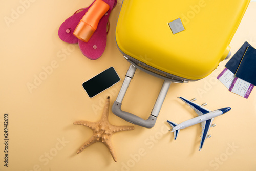 top view of yellow suitcase, plane model, starfish, sunscreen, flip flops, smartphone and tickets on beige background