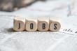 Leinwandbild Motiv Würfel mit Aufschrift JOBS auf einer Tageszeitung
