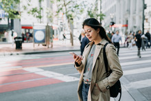 Cheerful Pretty Young Woman In Trendy Wear Walking On Street With Sunshine Enjoying Reading Sms With Good News On Smart Phone. Happy Asian Lady Holding Cellphone Standing On Zebra Crossing Road.