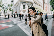 Female Asian Tourist With Curious Face Smiling Standing On Sidewalk. People Walking On Zebra Cross In Background. Young Woman Finding Direction City Tour In San Francisco In America Spring Holidays