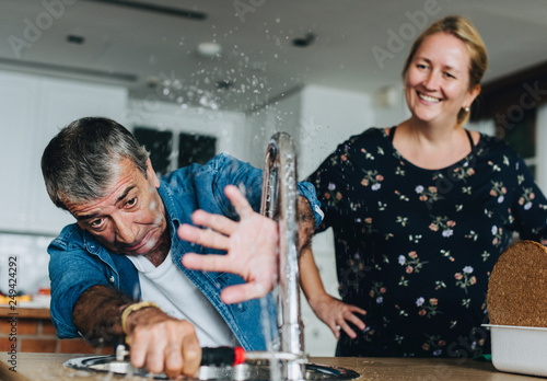 Fotomural  Couple fixing a kitchen sink