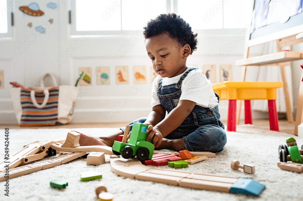 Fototapety, obrazy: Cute little boy playing with a railroad train toy