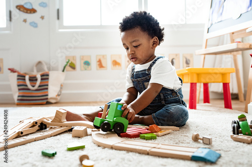 Fototapeta Cute little boy playing with a railroad train toy obraz
