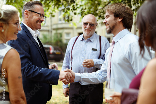 Fotografie, Obraz  Men shaking hands at a party