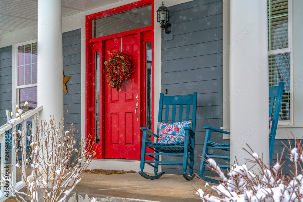 Fototapeta Winter view of home with red door and front porch