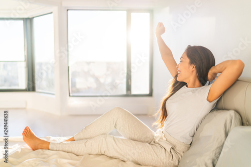 Morning woman waking up stretching in bed in sunshine sunrise early bird happy Asian girl in pajamas on weekend in sun glow Wallpaper Mural