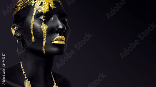 Young woman face with art fashion gold makeup. An amazing model with black and yellow creative makeup. Closeup portrait