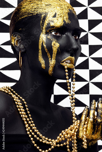 Young woman face with art fashion gold makeup. An amazing model with black and gold creative makeup. Fashion portrait. Black skin