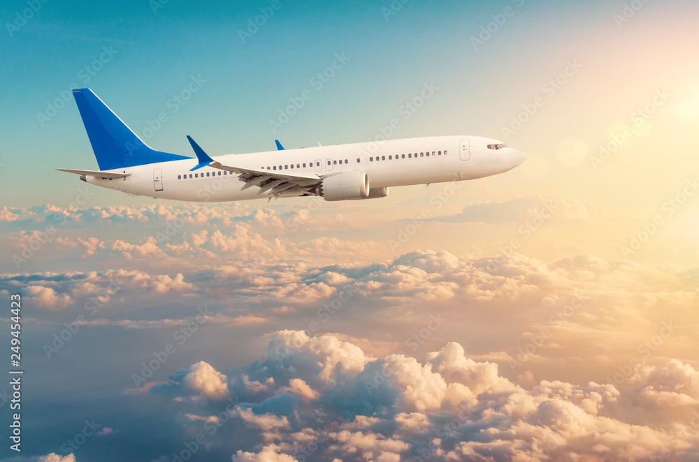 Fototapety, obrazy: Commercial airplane flying above cloudscape in dramatic toned sunset light