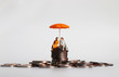 canvas print picture - An elderly miniature couple sitting with an umbrella on a pile of coins.