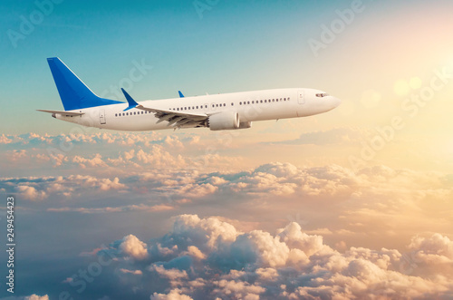 Commercial airplane flying above cloudscape in dramatic toned sunset light